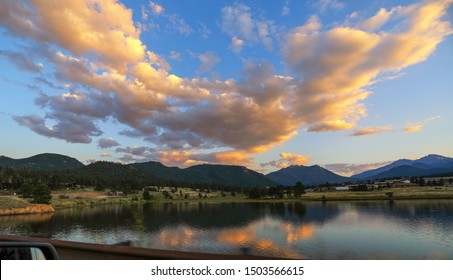 Breathtaking sunset view in late summer.  Estes Lake, Rocky Mountain National Park, Colorado, USA.  Reflection in water of colorful clouds, blue sky and mountains.