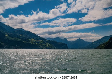 The breathtaking view across the lake with boats on it and mountains in the background in Switzerland