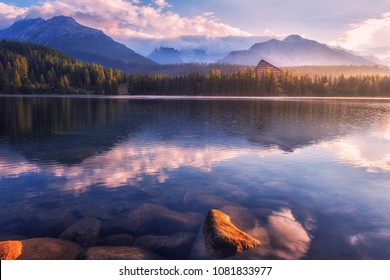 Breathtaking view of the alpine lake and mountains with reflection in the crystal clear water before sunrise. Famous tourist resort lake Strbske Pleso in the High Tatras, Slovakia (Slovensko), Europe