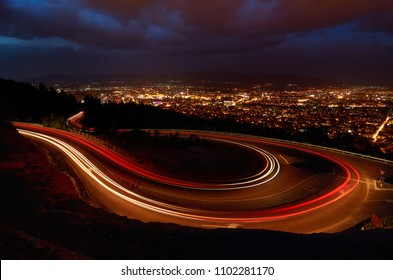 Breathtaking view of light streaks over road and night cityscape of Skopje in distance. Macedonia.