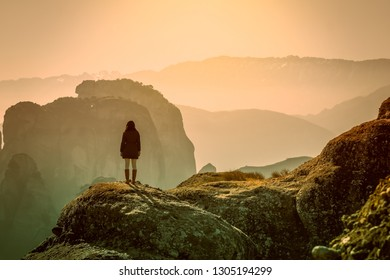 Breathtaking view of Meteora in Greece with a woman standing on a rock