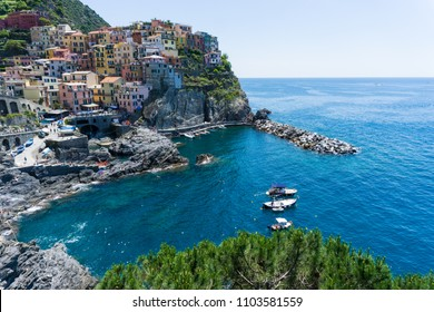 Breathtaking view on Manarola Village, Cinque Terre Coast of Italy, boats in the sea. Manarola is a beautiful small town in the province of Liguria,Italy and famous travel attraction for tourists.