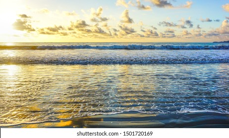 Breathtaking view over the ocean waves during high tide, making a natural reflection of clouds, golden bright sun lights while setting down. Scenic natural landscape wallpaper background.
