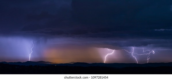 Breathtaking view of powerful thunderstorm over hills in evening