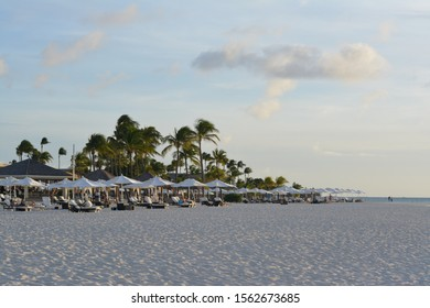 Breathtaking view of the romantic Bucuti & Tara Resort off of Manchebo Beach on Eastern side of Aruba with palm trees, white beach umbrellas, a   few clouds and beautiful white sand before sunset