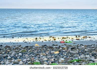 breathtaking view of sandy beach and colorful rocks with blue sea and sky in the background