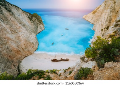 Breathtaking view of Shipwreck middle of sandy Navagio beach surrounded by azure deep turquoise sea saltwater and huge white cliff limestone rocks. Zakynthos island, Greece