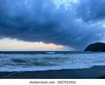 Atematemberaubende Sicht auf das stürmische Mittelmeer, dramatische Sonnenuntergangsblüten mit Wolken und Strandlandschaft in Ligurien, Italien