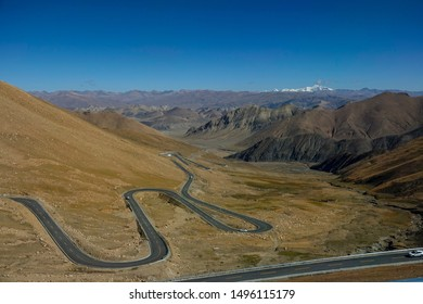 Breathtaking view of a winding mountain road leading across the Tibetan Plateau. Asphalt road leads tourists along the steep mountains in the Himalayas. Scenic view of a mountain road in sunny Tibet.