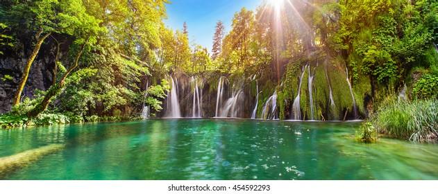Panorama de cachoeiras de tirar o fôlego no Parque Nacional dos Lagos Plitvice, Croácia, Europa. Vista majestosa com água turquesa e sol raios ensolarados, destinos de viagem fundo