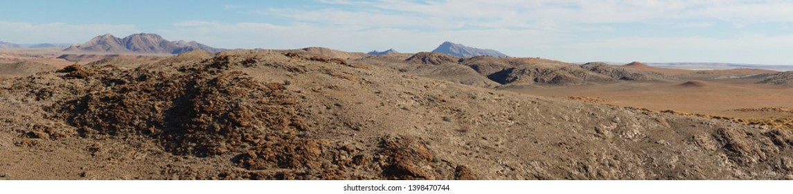 A breathtakingly beautiful untouched desert landscape with many dark brown rocks and dried up hills seems to be a hostile environment. Some mountains and a clear blue sky are in the background.