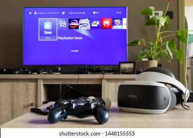 Brecht, Antwerp, Belgium - June 6 2019: A playstation 4 controller and some move controllers with a virtual reality headset on a table in front of a television showing the playstation home screen.