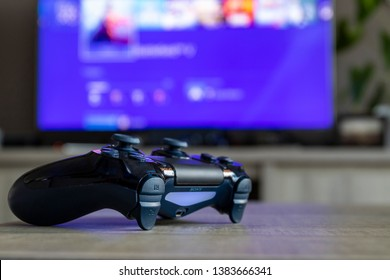 BRECHT, BELGIUM-MARCH 28 2019: A portrait of a Playstation 4 controller, which is turned on, in front of a blurred television showing the Playstation home screen.