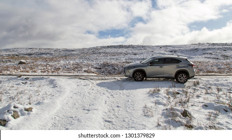 Brecon Beacons, UK: January 30, 2019: A Lexus NX 300h F-Sport crossover hybrid car on the road side in snow and dangerous icy conditions with copy space.