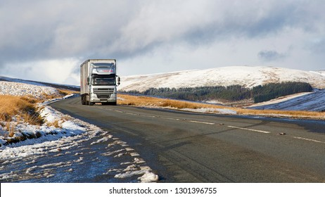 Brecon Beacons, UK: January 30, 2019: A large Daf semi truck drives on the A4059 mountain road in winter snow and dangerous icy conditions.