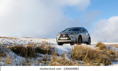 Brecon Beacons, UK: January 30, 2019: A Lexus NX 300h F-Sport crossover hybrid car on the road side in snow and dangerous icy conditions. Panoramic with copy space.