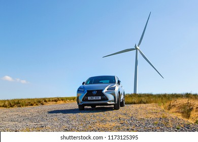 Brecon, UK: July 07, 2018: A new Lexus NX 300h F-Sport crossover hybrid car parked under a wind turbine in a rural location with a blue sky background in a horizontal format with copy space.