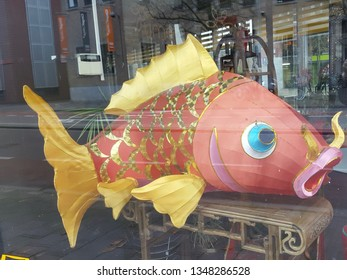 """Breda / the Netherlands - 12/18/2015: Koinobori """"carp streamer"""" or wind sock in pink and gold, so big that it can't fly, placed on a support behind glass."""