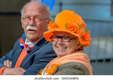 BREDA, NETHERLANDS - April 27, 2015: Unidentified older woman with gray hair, orange party hat and an ornage scarf poses for the photographer in front of her husband; it is King's Day in Breda.