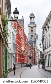 BREDA, THE NETHERLANDS - AUGUST 15, 2018: Sint Janstraat in the city center of Breda with the tower of St. Anthony of Padua Cathedral is the Roman Catholic cathedral of the Diocese of Breda.