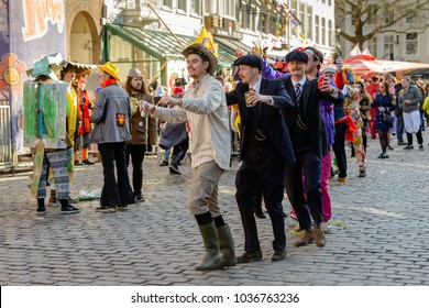 BREDA, NETHERLANDS - FEBRUARY 10, 2018: Outdoor shot of a row of unidentified costumed men  dancing a polonaise on a square with a glass of beer in their hands; it is carnival in the city.