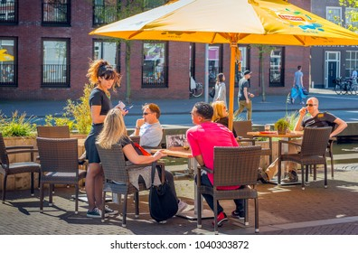 BREDA, NETHERLANDS - May 5, 2016:  An unidentified waitress list the order of the guests at the terrace table of a cafe in the center of the Dutch city of Breda.