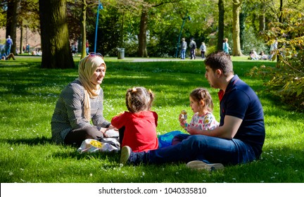 BREDA, NETHERLANDS - May 5, 2016:  An undentified young Iraqi refugee family celebrates the Dutch National Liberation Day sitting and picnicing in the grass of the Valkenberg Park in Breda.
