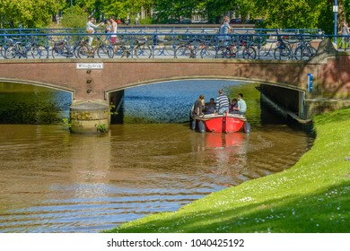 BREDA, NETHERLANDS - May 5, 2016:  Unidentified young people sailing on the National Liberation Day with a red boat in the water of a canal under the Willemsbrug in the center of the city of Breda.