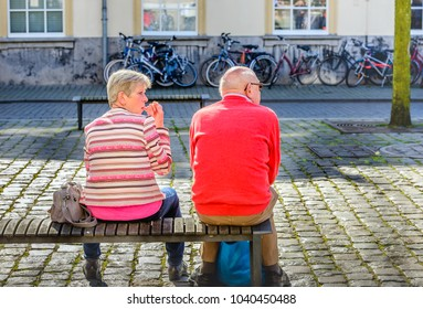 BREDA, NETHERLANDS - May 5, 2016: An unidentified older man and woman sit together on a wooden bench on the Kasteelplein in the city of Breda while they look around.