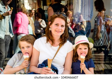 BREDA, NETHERLANDS - May 5, 2016: Street portrait of an unidentified mother and her children eating an ice cream together sitting at a bench against the reflective shop window of an ice cream shop.