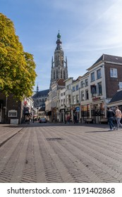 Breda, The Netherlands - September 29, 2018: De grote kerk located in central Breda, with people and shops in the foreground
