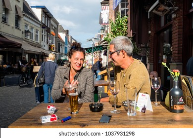 BREDA, NETHERLANDS - september 5, 2015: Outdoor portrait of an unidentified smiling woman and a man talking and sitting at a terrace table of a cafe in the center of the Dutch city of Breda.