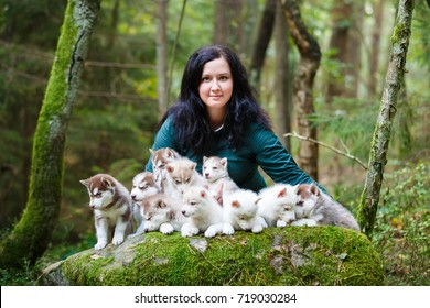 Breeder of dogs with their pets in a forest