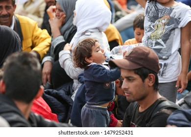 Bregana, Slovenia - September 20, 2015 : A small syrian child drinking water out of a bottle among refugees at the slovenian border with Croatia.