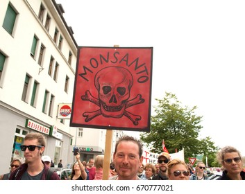 """BREGENZ, AUSTRIA - MAY 20, 2017: A man holds a red transparency with a dead head and with the headline: """"Monsanto"""" at the demonstration event """"March Against Monsanto"""" 2017 in Bregenz, Austria"""