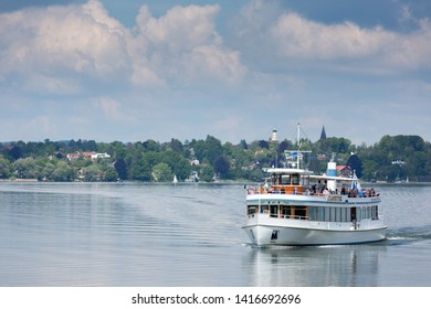 """BREITBRUNN, BAVARIA / GERMANY - May 30, 2019: Ship with the name """"Augsburg"""" cruising on Lake Ammersee on a sunny spring day. Ammersee is a popular travel destination for tourists."""