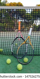 Brela.  Croatia - Augest 9, 2019: Attributes of the game of tennis.  Two tennis rackets and tennis balls on an outdoor court in summer near the net against the backdrop of a pine forest and the sea