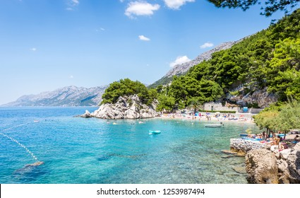 BRELA, CROATIA - JULY 20, 2018: Tourists relaxing on marvelous Brela beach, beautiful Mediterranean seascape in Croatia