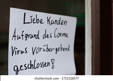 """Bremen, Deutschland - 04/12/2020: Sign saying """"Due to corona Virus temporarily closed."""" at a store front during pandemic for distance and infection rate reduction"""