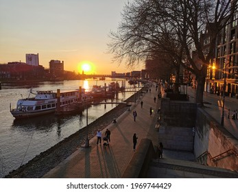 Bremen, Germany - April 16 2021: Weser river flowing along Schlachte promenade. Passing Stephani church and new built buildings. Beautiful sunset over harbor with boat and marina.