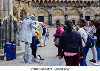 Bremen, Germany - August 22, 2017: Tourists in the market square with a living statue as a photo motif