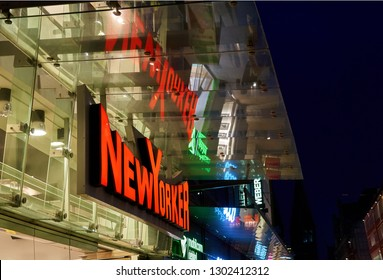 """Bremen, Germany - February 01, 2019: logo of the company """"New Yorker"""" over a store during blue hour at dawn, the red neon writing is colorfully reflecting in a vitrine roof"""
