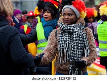 Bremen, Germany - February 03 2018: pretty young african lady with big black and white scarf, brown plush jacket and toupee in german colors offers flyers to the public while carnival parade