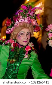 """Bremen, Germany - February 22, 2019: beautiful woman with green dress, blonde toupee and fancy pink hat with flowers, butterflies and feathers at the event """"Lichtertreiben"""" during samba carnival"""