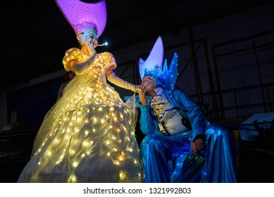 Bremen, Germany - February 22, 2019: man with fancy blue carnival costume kisses gently the hand of a woman with beautiful dress and hat with led lights while he is sitting, both are on stilts