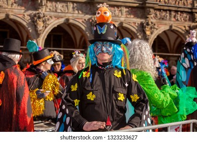 Bremen, Germany - February 23, 2019: funny man with blue toupee and black overall and top hat decorated with yellow and blue butterflies and a plush clown fish during samba carnival