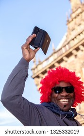 Bremen, Germany - February 23, 2019: young african man with funny red toupee holds his smartphone in the air and smiles brightly