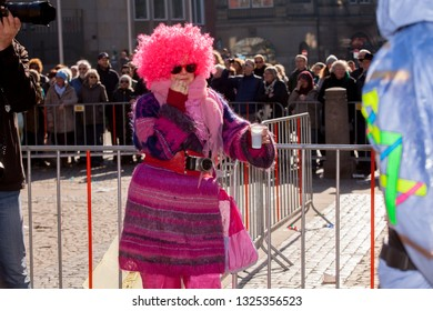 Bremen, Germany - February 23, 2019: funny woman with sunglasses, neon pink toupee and knitted dress in matching colors leans at a fence with a drink in plastic cup