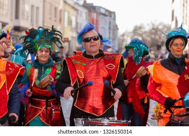 Bremen, Germany - February 23, 2019: samba group with drums and colorful red costumes and blue hats or toupees during carnival parade