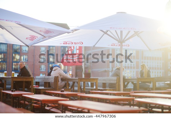 BREMEN, GERMANY - MARCH 23, 2016: Tourist having a beer in a restaurant on an embarktment of Weser river in Bremen